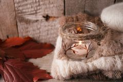 Warm sweater on wooden rustic bench, Candle and leaves, Quiet cozy homely scene. Fall autumn weekend. Still life details of living room. Rustic wooden background royalty free stock photos