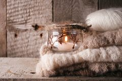Warm sweater on wooden rustic bench, Candle, Quiet cozy homely scene. Fall autumn weekend. Monochrome concept. Warm sweater on wooden rustic bench, Candle stock image