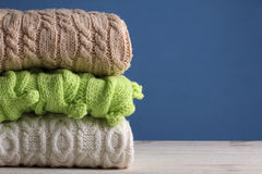 Warm sweaters. Stack of warm sweaters on wooden table on blue background Royalty Free Stock Photography