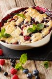 Warm sweet cobbler of raspberries and blueberries close-up in a. Baking dish on a table. vertical Stock Photos