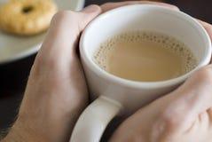 Warm tea. Warming hands on a large mug of white tea Royalty Free Stock Photo