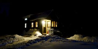 Warm Tiny House. Tiny house aglow with warmth in the winter Stock Images