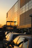 Warm tobacco color sunset immuminates building and car windows royalty free stock photography