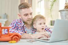 Father and Son Playing Games. Warm toned portrait of handsome father teaching son how to use laptop or playing computer games together, focus on excited little Stock Photos