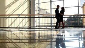 Warm tones footage: two young people meet in business center.  stock footage