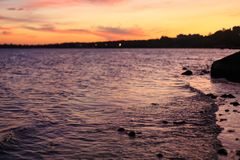 The warm tranquil sea waves at sunset in summer evening Stock Image
