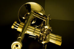 Warm Trumpet. A silver trumpet with gold trim on a dark surface with a golden tone Stock Image