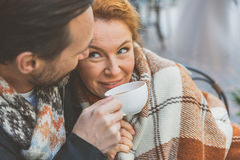 Warm up by this beverage and my love. Loving men is giving cup of hot tea to his wife. Woman is sitting covered by blanket and smiling. They are embracing Royalty Free Stock Image