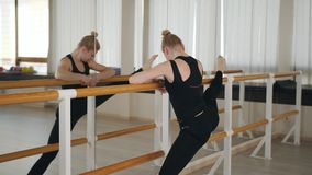 A woman dancer or a ballerina standing at a ballet barre in front of the mirror and does some stretching. Woman dancer stock footage