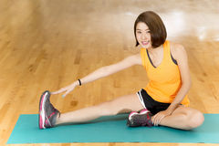 Warm up Exercise. An Asian lady doing her warm up stretching exercise by reaching to her feet in a gym Royalty Free Stock Photo