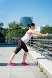 Warm up before jogging. Young sport woman is stretching leg before jogging - outdoor in city stock images