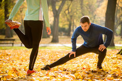 Warm up before running. Young couple stretching legs before running in autumn nature Royalty Free Stock Photo