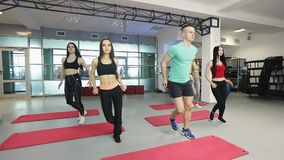 Warm up before training. Fitness instructor is working with group of young women in fitness gym. Steady cam shot stock video footage
