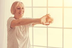 Cheerful aged woman doing stretching exercises. Warm up. Waist up of a cheerful aged woman holding the hands on front of her and doing stretching exercises while Stock Image