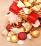 Warm weather Christmas. Gift wrapped box full of shells at the beach Stock Photo