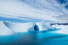 Warm weather melting the ice of the Matanuska Glacier into a large blue pool. An ice cave cuts into the ice, also flooded with the. Crystal blue water flooded an royalty free stock photo