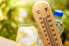 Warm weather. Refresh drink with thermometer, concept warm weather stock images
