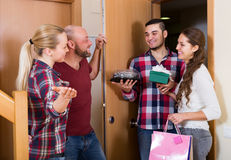 Warm welcome of smiling friends. Holding gifts and sweets Stock Photography