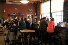 Tasting room with several people gathered to catch up on life, Black Button Distillery, Rochester, New York, 2017. Warm and welcoming tasting room, where friends royalty free stock photos