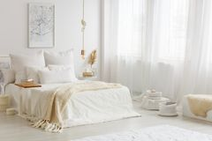 Beige blanket on white bed. Warm, white and gold bedroom interior with beige blanket on white sheets of the bed stock photography
