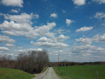 Warm Winter day. Beautiful winter on the back roads driving past the farm with big fluffy clouds Stock Image