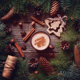 The warm winter drink. Cocoa or cappuccino in the festive decorations with Christmas tree and pine cones. Square format. The warm winter drink. Cocoa or royalty free stock images