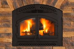 Warm Winter Fire with wood, flames, ash, embers and charcoal. Black Iron and Stone Fireplace Stock Images