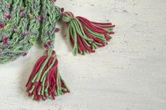 Warm winter scarf with  colored pompoms Royalty Free Stock Photos