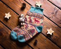 Warm winter socks. Hand-knitted with a traditional winter pattern of deer and Christmas tree on a wooden floor Stock Photo