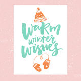Warm winter wishes. Christmas card design. Vector typography with hand drawn illustrations of hat and mittens.  Stock Photos
