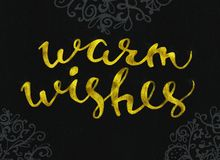 Warm wishes Gold glittering elegant modern brush lettering design on a black background rastr.  Stock Photo