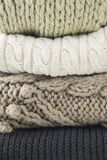 Warm woolen knitted winter and autumn clothes, folded in a pile. Sweaters, scarves. Close-up. Warm woolen knitted winter and autumn clothes, folded in a pile royalty free stock photos