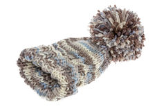Warm woolly winter hat with a huge pompom. Hand-knitted from mottled grey wool on a white background Royalty Free Stock Image