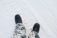 Warme Arbeitsschuhe auf dem Hintergrund einer schneebedeckten Straße lizenzfreie stockbilder