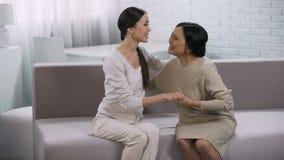 Warme Beziehungen zwischen den Frauen, Tochter und Mutter, die zu Hause auf Couch umarmen stock footage