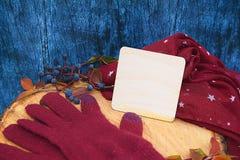 Warme Burgunder-Handschuhe mit einem Schal und einem Hut auf blauer Farbe des hölzernen Hintergrundes mit Herbstlaub und verringe Stockbilder