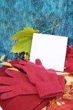 Warme Burgunder-Handschuhe mit einem Schal und einem Hut auf blauer Farbe des hölzernen Hintergrundes mit Herbstlaub und verringe Stockfotografie