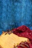 Warme Burgunder-Handschuhe mit einem Schal und einem Hut auf blauer Farbe des hölzernen Hintergrundes mit Herbstlaub und verringe Lizenzfreies Stockfoto