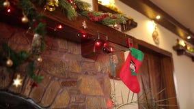 Warme comfortabele die steenopen haard voor Kerstmis met kroon, kousen, slingerlichten wordt verfraaid Schoorsteenmantel met deco stock video