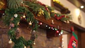 Warme comfortabele die steenopen haard voor Kerstmis met kroon, kousen, slingerlichten wordt verfraaid Schoorsteenmantel met deco stock footage