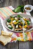 Warme de herfstsalade met aardappels, paddestoelen, bacon, spinazie, mosterdsaus en kaas op oranje servet Houten oude achtergrond Stock Afbeelding