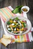 Warme de herfstsalade met aardappels, paddestoelen, bacon, spinazie, mosterdsaus en kaas op oranje servet Houten oude achtergrond Royalty-vrije Stock Afbeeldingen