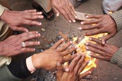 Warme de mensen overhandigt de brand in India stock foto's