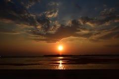 Warme dramatische zonsondergang bij een strand tijdens eblandschap Stock Foto