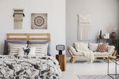 Warme ethnoslaapkamer met het comfortabele bed van de koningsgrootte, elegant sofa en macramé op de muur royalty-vrije stock afbeeldingen