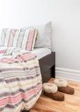 Warme gemütliche Pantoffel nähern sich Bett Lizenzfreie Stockfotos