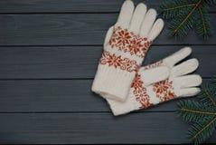 Warme Handschuhe oder Handschuhe mit Tannenzweigen auf hölzernem Hintergrund Lizenzfreie Stockfotos