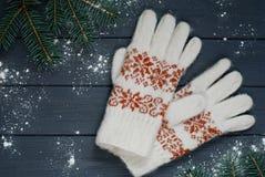 Warme Handschuhe oder Handschuhe mit Tannenzweigen auf hölzernem Hintergrund Stockfotos