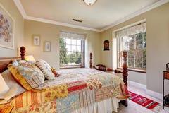 Warme kleurenslaapkamer met een ouderwets bed Stock Afbeelding
