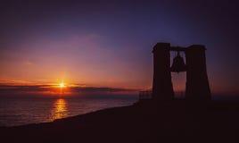 Warme mooie zonsondergang met de contour van de klok Stock Afbeelding